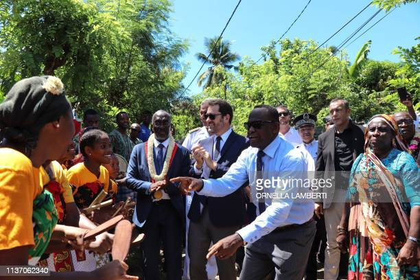 French Interior Minister Christophe Castaner flanked by Mayor of Dzaoudzi municipality Said Omar Oili is welcomed by musicians and dancers as he...