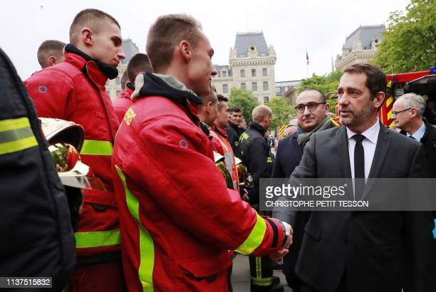 French Interior Minister Christophe Castaner greets French fire fighters outside NotreDamede Paris in the aftermath of a fire that devastated the...