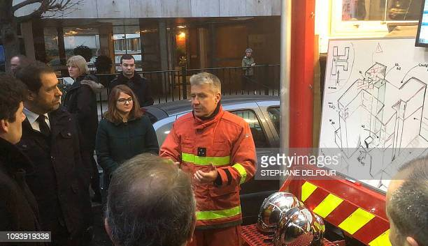 French Interior minister Christophe Castaner listens to a firefighter talking in front of the plan of a building where a fire killed 8 in Erlanger...