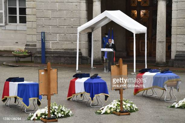 French Interior Minister Gerald Darmanin delivers a speech as he stands before three of the five caskets of police officers and members of SAF who...