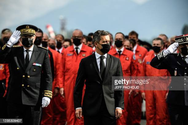 French Interior Minister Gerald Darmanin , wearing a mask, leads a ceremony in Le Versoud Aerodrome, Southeastern France, on September 17 to pay...
