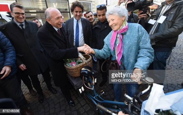 French Interior Minister Gerard Collomb flanked by Libourne Mayor Philippe Buisson greets an elderlly woman with a bicycle after visiting the...