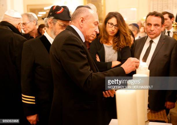 French Interior Minister Gerard Collomb lights a candle in The Synagogue des Tournelles in Paris on March 28 during a service in memory of Mireille...