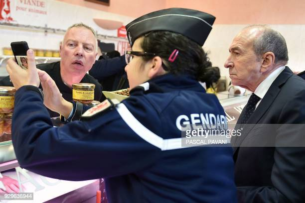 French Interior Minister Gerard Collomb listens as a gendarme showing him a phone application at a boutique during his visit on March 9, 2018 in...