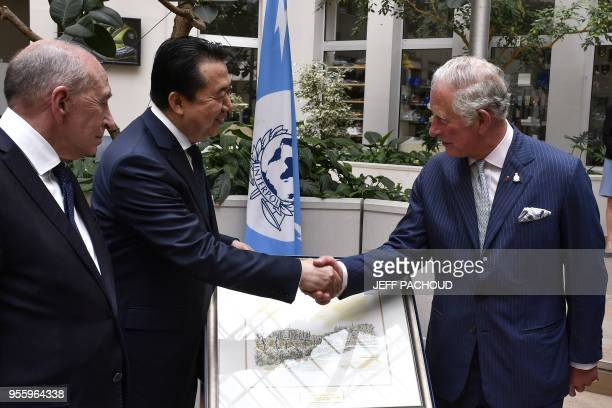 French Interior Minister Gerard Collomb looks on as Britain's Prince Charles the Prince of Wales shakes hands Interpol' president Meng Hongwei during...