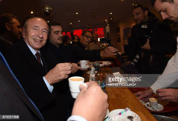 French Interior Minister Gerard Collomb smiles as he drinks a coffee in a cafe after visiting the gendarmerie of Libourne on November 17 to launch...