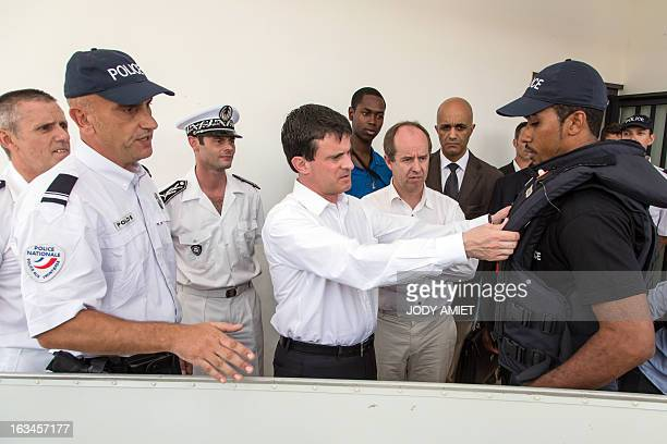 French Interior minister Manuel Valls adjusts a bulletproof vest tested by a police officer as he visits the Police headquarters of SaintGeorges de...