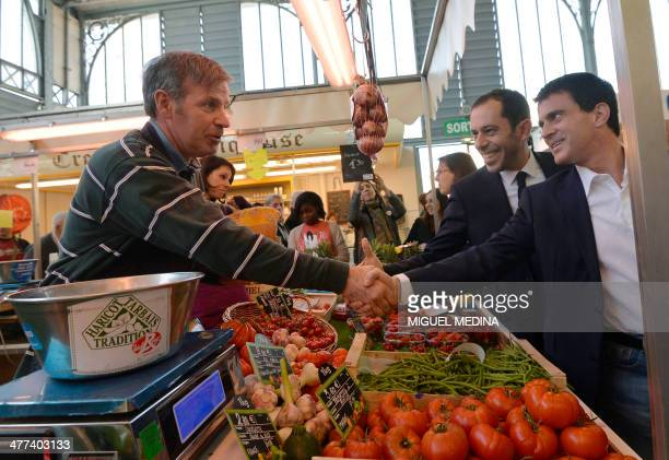 French Interior Minister Manuel Valls shakes hans with a fruit vendor next to socialist party's candidate Carlos da Silva at the Central market in...