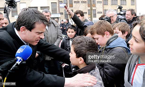 French Interior Minister Manuel Valls talks to a young boy as he meets local residents of the 'Amiens Nord' classified security priority zone on...