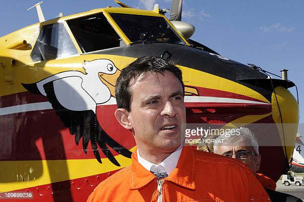French Interior Minister Manuel Valls wears a jumpsuit after going onboard a Canadair plane as he visits on May 31, 2013 in Marignane, southern...
