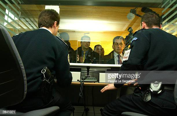 French Interior Minister Nicolas Sarkozy speaks with immigration policemen at Charles de Gaulle airport terminal 2 E on January 2 2004