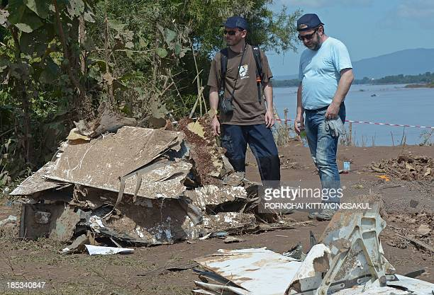 French investigators inspect pieces of debris at the site of the Lao Airlines plane crash near the Mekong river in Pakse town on October 19 2013 Lao...