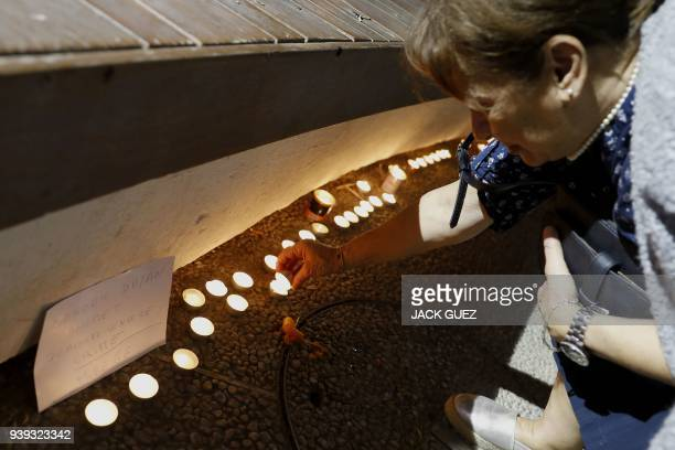A French Israeli lights candles during a gathering in the city of Netanya on March 28 in memory of Mireille Knoll an 85yearold Jewish woman murdered...