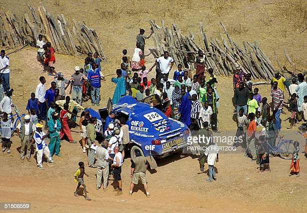 French JeanLouis Schlesser next to his MeganeSchlesser is surrounded by Senegalese villagers 19 January 2001 after the 18th stage of the ParisDakar...