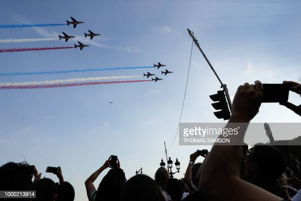 French jet fighters trailing smoke in the colours of the national flag fly over the Champs Elysee as supporters welcome players of the French...