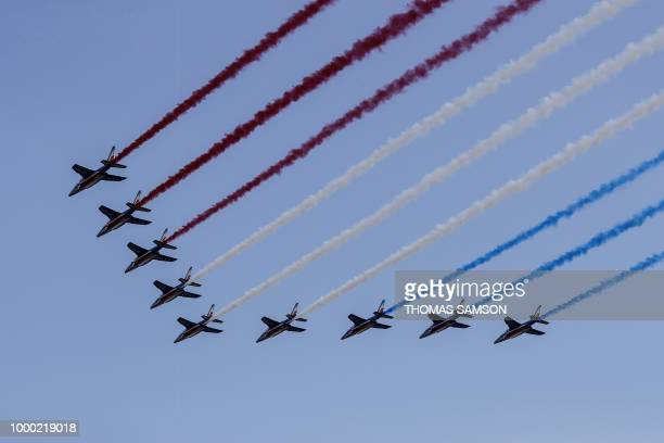 French jet fighters trailing smoke in the colours of the national flag fly over the Champs Elysee welcoming players of the French national football...