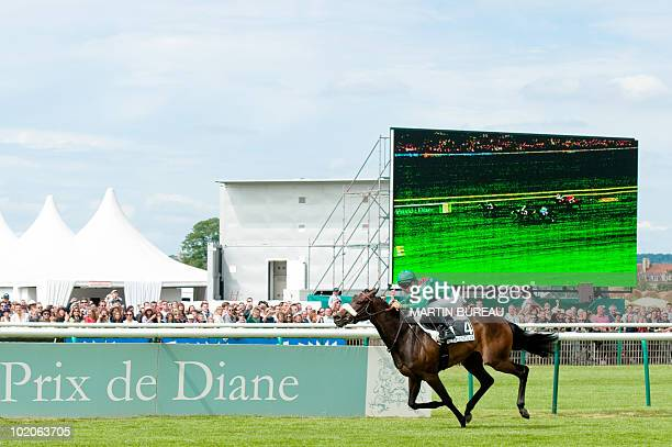 French jockey ChristophePatrice Lemaire riding Aga Kahn's Sarafina crosses the finish line to win the 161th Prix de Diane horse racing on June 13...
