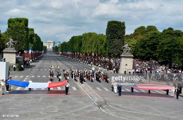 A French jointarmy brass band performs as the French and US national flags are unfolded at the end of the annual Bastille Day military parade on the...