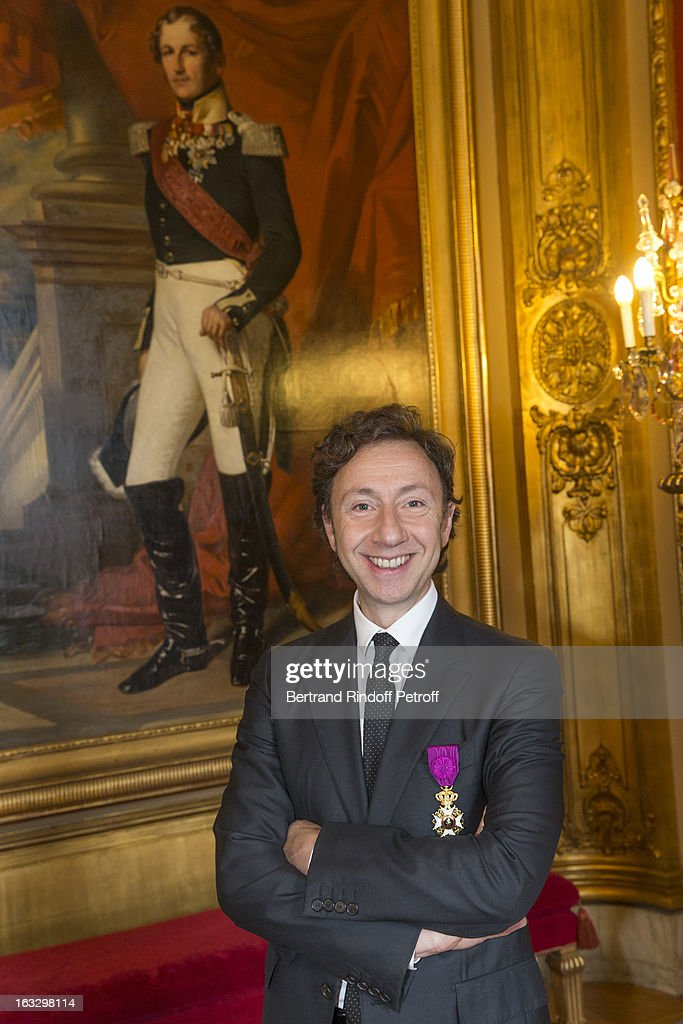 French journalist and author Stephane Bern poses by a painting of King Leopold I of Belgium after he was appointed officer in the King Leopold order during a ceremony at Palais d'Egmont on March 7, 2013 in Brussel, Belgium.