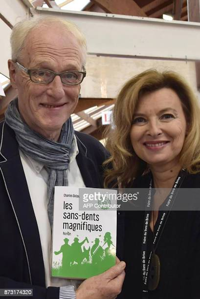 French journalist and fomer France's first lady Valerie Trierweiler poses with French writer Charles Delpy holding his book during the 36th edition...