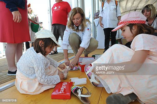 French journalist and former first lady of France Valerie Trierweiler offers shoes to children during the Solitaire du Figaro sailing race off the...