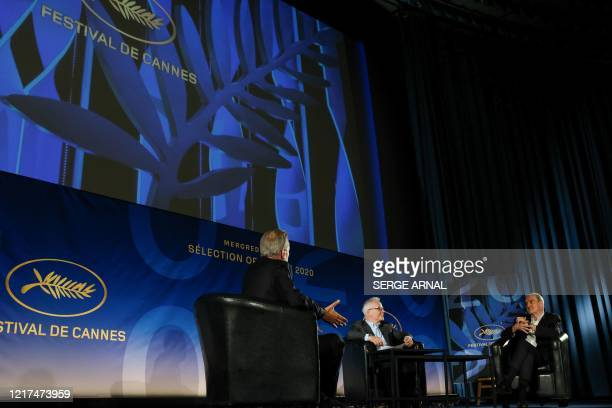 French journalist Laurent Weil Cannes Film Festival's director Thierry Fremaux and President Pierre Lescure talk on stage during the unveiling of the...