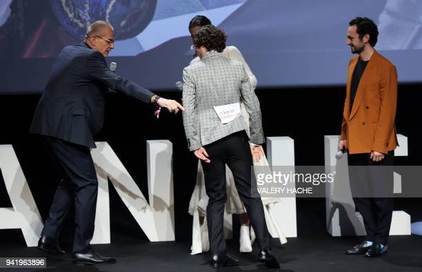 French journalist Laurent Weil shows British actor Alexander Vlahos his seat name tag that remained attached to his jacket as he arrives on stage...