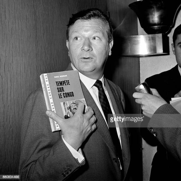 French journalist Marcel Niedergang poses with his book 'Tempête sur le Congo' after winning the 1961 Albert Londres prize on May 16 in Paris / AFP...