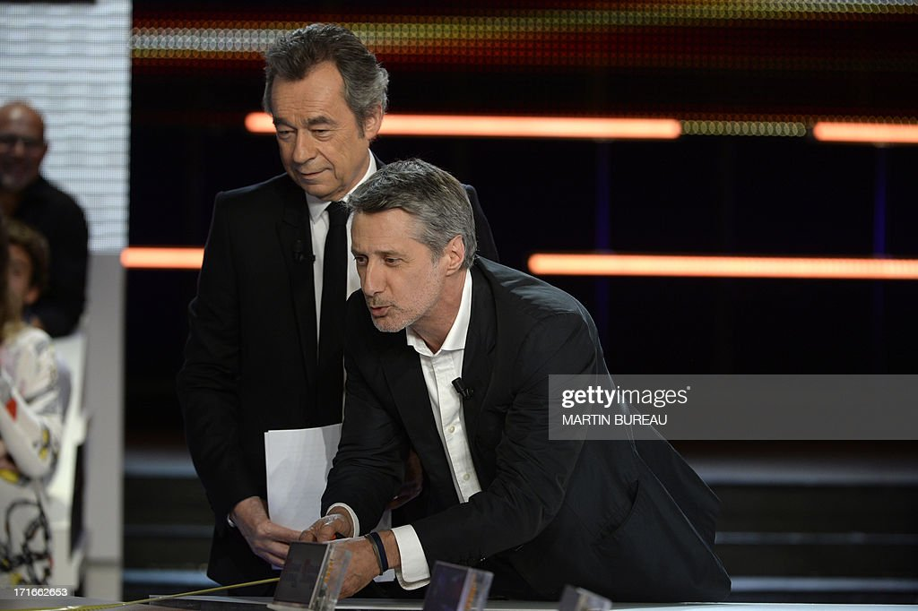 French journalist Michel Denisot (L) stands by his successor Antoine de Caunes on the set of French TV Canal+ talk show 'Le Grand Journal,' he anchored for the last time on June 27, 2013 in Paris.