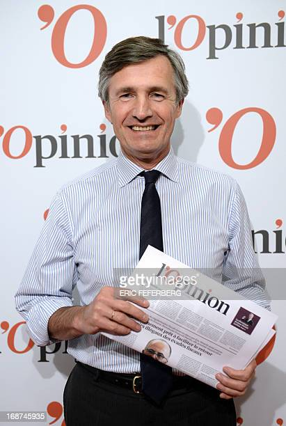 French journalist Nicolas Beytout poses with a copy of the first edition of his daily newspaper L'Opinion on the eve of its launch on May 14 2013 in...