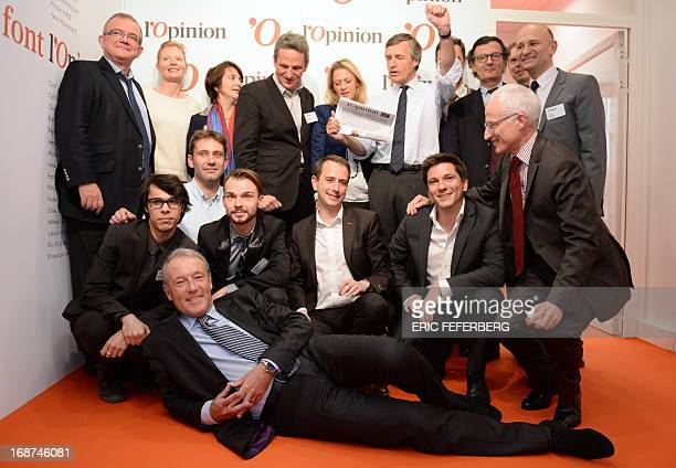 French journalist Nicolas Beytout poses with his team and a copy of the first hardcopy edition of the daily newspaper L'Opinion during the launch of...