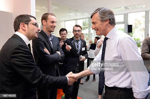 French journalist Nicolas Beytout shakes hands with unidentified members of several ministry cabinet during the preparation of the first edition of...