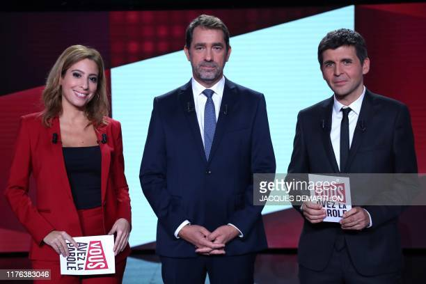French journalists Lea Salame and Thomas Sotto pose with French Interior Minister Christophe Castaner prior to the start of the political TV show...
