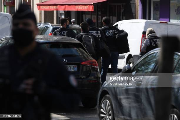 French judiciary police investigators cordon off the scene, after several people were injured near the former offices of the French satirical...