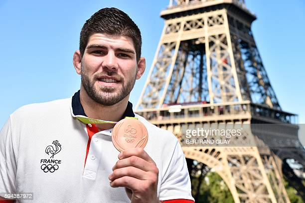 French judoka Cyrille Maret poses with his bronze medal on August 23 in front of the Eiffel tower in Paris France's Olympic team landed in Paris on...