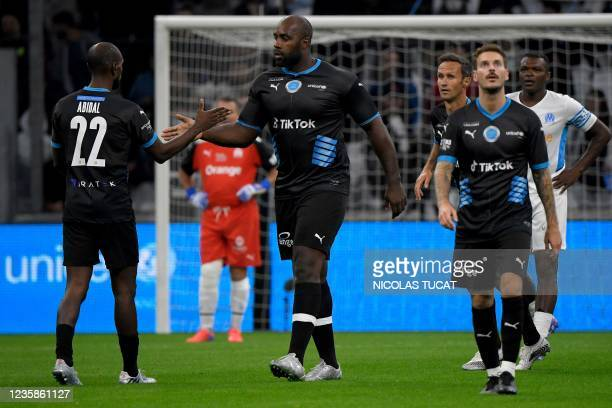 """French judoka Teddy Riner checks with French former football player Eric Abidal during the charity """"Heroes"""" football match between former Olympique..."""