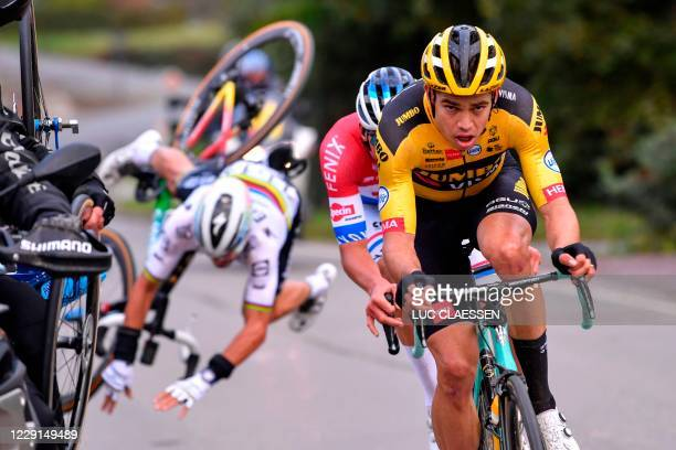 French Julian Alaphilippe of Deceuninck - Quick-Step falls after touching a motorcyclist, as he rides behind Belgian Wout Van Aert of Team...