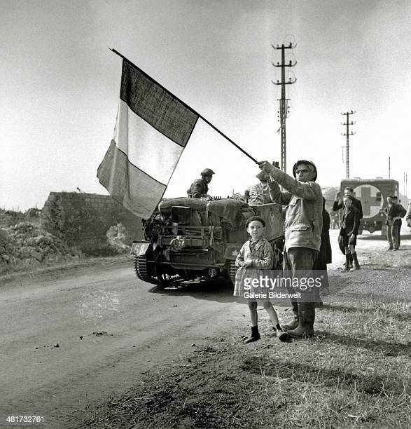 French June 1944 of the first World War with a French flag salutes Canadian troop transport vehicles of the South Saskatchewan Regiment of the 2nd...