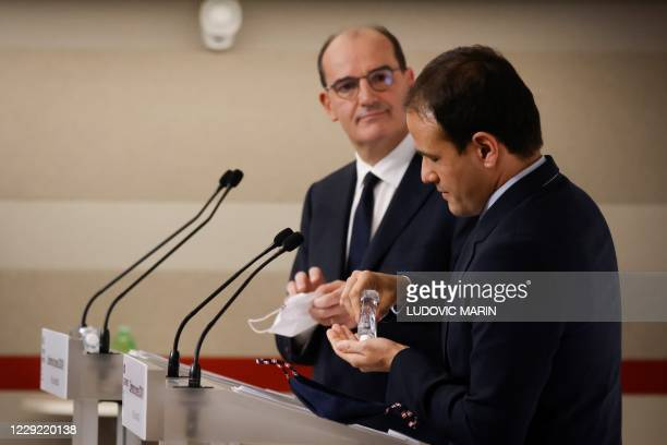 French Junior Minister for Digital Transition and Electronic Communication Cedric O puts on hydrolic gel next to French Prime Minister Jean Castex...