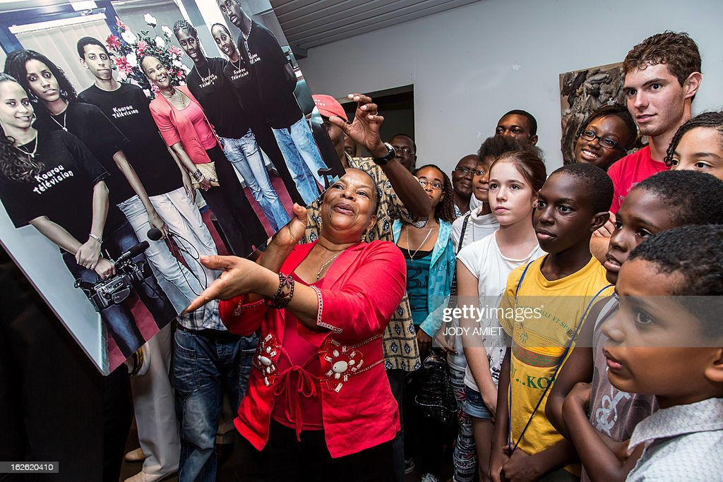French Justice minister Christiane Taubira (C) holds a photography showing her posing with young people at the time of the launch of Kourou Television, on February 23, 2013 during a meeting at Kourou's city hall, as part of her five-day visit to the French French overseas territory of Guiana.