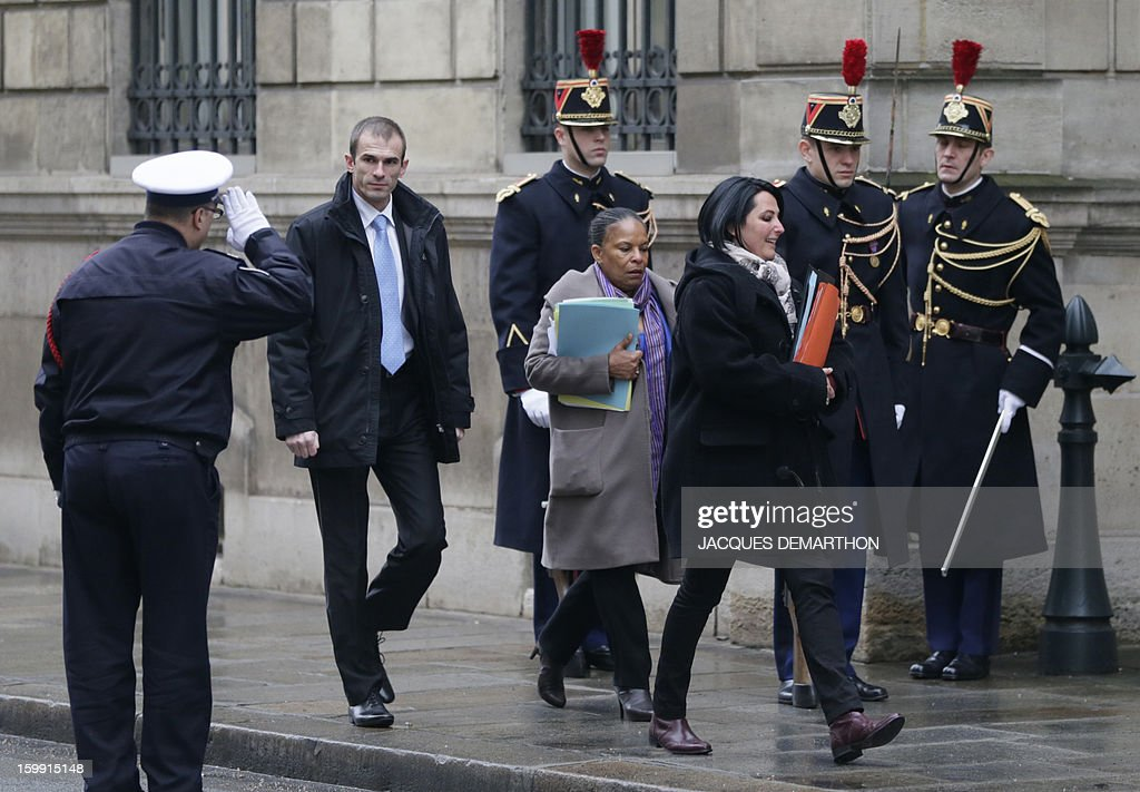 French justice minister Christiane Taubira (C) walks past a saluting police officer as she arrives at the Elysee Palace to take part in a ministerial meeting on January 23, 2013 in Paris. DEMARTHON