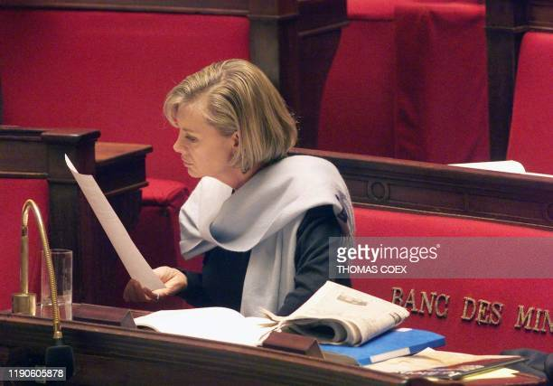 French Justice Minister Elisabeth Guigou reads the news 08 November 1998 at the Parliament in Paris as MP's began another round of fierce debate on...