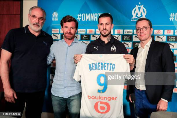 French L1 football club Olympique de Marseille's newly recruited Argentina forward Dario Benedetto poses with his new jersey flanked by Marseille's...