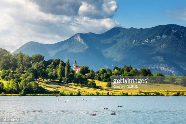 french landscape with small church steeple along rhone river and grand colombier bugey alps mountains in summer in auvergne-rhone-alpes - auvergne rhône alpes stock pictures, royalty-free photos & images