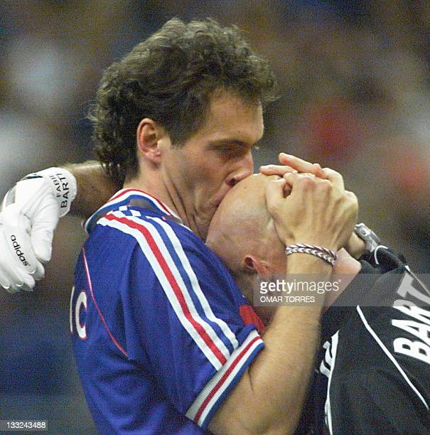 French Laurent Blanc kisses the head of goalkeeper Fabien Barthez 12 July at the Stade de France in Saint-Denis, near Paris, after France defeated...