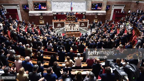 French lawmakers applaud the end of a speech by Canadian Prime Minister Justin Trudeau at the French National Assembly in Paris on April 17 as part...