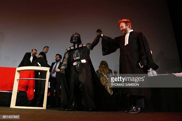French lawyer Antoine Vey holds the hand of a person wearing a Darth Vader costume during the Darth Vader's trial event at the Grand Rex movie...