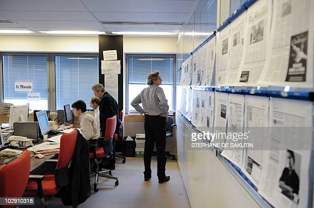 French leading newspaper Le Monde's head of editorial board Alain Frachon looks at the pages of its next issue on a wall of the editorial office on...