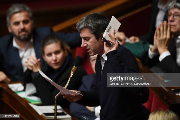 French leftist La France Insoumise party member of Parliament Francois Ruffin holds a check book as he speaks during a session of questions to the...