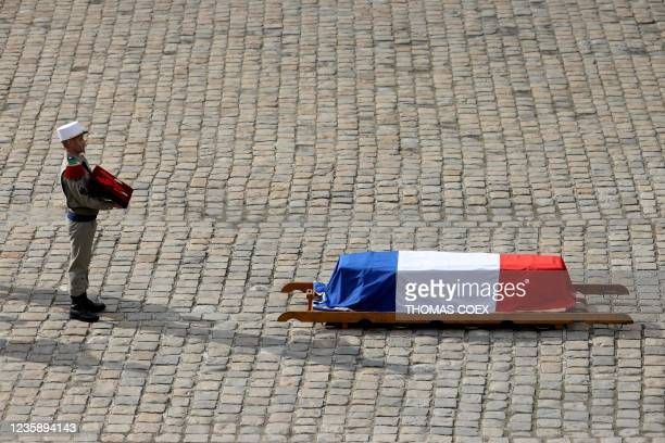 French legionnaire carries Hubert Germain's medal of Honour, as he stands behind his coffin during a national memorial service for him - the last...